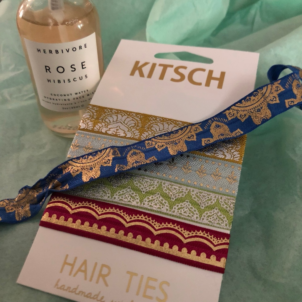 Spray bottle of rose hibiscus water next to package of kitsch hair ties